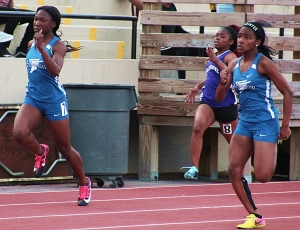 Stephenson's Marisa Mayfield (far right) moves in front in the 100 meter dash as teammate Amanda King (far left) and Miller Grove's Travyonna Manuel work hard to keep up. (Photo by Mark Brock)