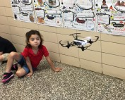 A Pre-K student looks on as a drone flies the hallway.