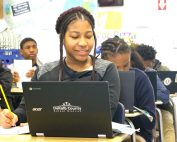 female student smiles while looking at laptop