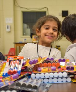 girl smiles at camera while school supplies lay on table