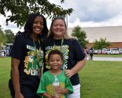 Kelley Lake Elementary staff pose with student at Exchange Park