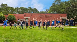 group of students jump in front of Austin Elementary