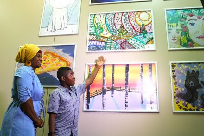 student points to artwork on wall while mom smiles in background