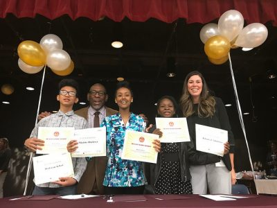 students hold certificates with superintendent