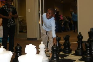 boy plays life-sized chess game