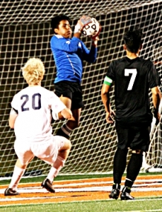 Cross Keys sophomore goalie Eduardo Cabrera (with ball) makes a big save to keep his team within 1-0 of St. Pius at the half. (Photo by Mark Brock)
