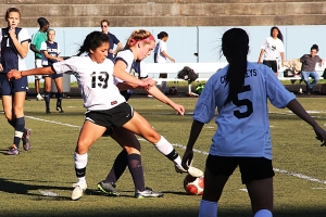 Cross Keys' Miriam Espino (19) battles a St. Pius player for the ball. (Photo by Mark Brock)