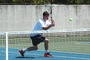 Dunwoody's JT Melton hits a backhand return in the No. 1 doubles match victory with Daniel Bynum.  (Photo by Mark Brock)