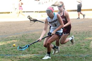 Dunwoody's Jenna Hogan (1) grabs a ground ball ahead of a Union Grove defender. (Photo by Mark Brock)