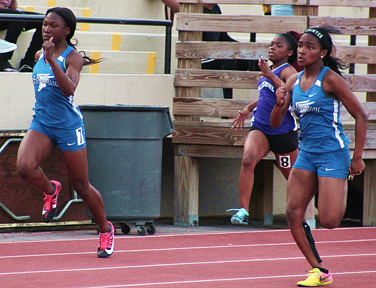 Stephenson's Marisa Mayfield (far right) moves in front in the 100 meter dash as teammate Amanda King (far left) and Miller Grove's Travyonna Manuel work hard to keep up.
