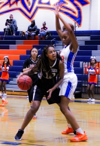 Lithonia's Zaryanna Mitchell (12) looks for room to score against Columbia defender A. Maddox. Columbia won the Region 5-5A contest 69-22. (Photo by Mark Brock)