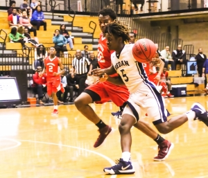 Redan's Javen Flowers-Smith (5) drives against Stone Mountain's Samari Moore (22) during the Region 5-3A Tournament game. (Photo by Mark Brock)