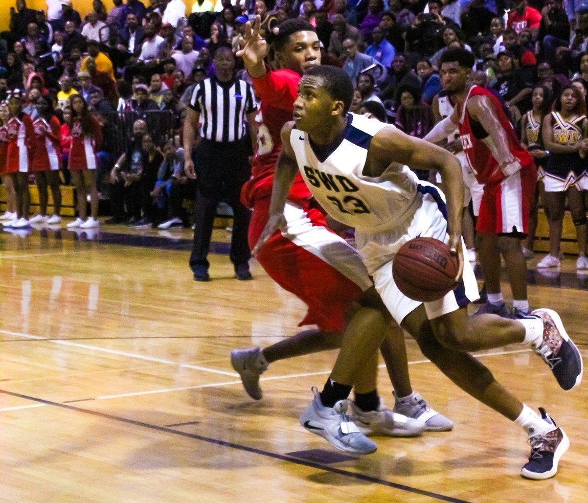 Southwest DeKalb's James Glisson (23) spins on the baseline for a reverse layup against Woodland's Sincere Whitehead (25). (Photo by Mark Brock)