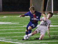 Dunwoody's Joshua Hitt (24) gets pulled down by a North Atlanta defender. (Photo by Mark Brock)