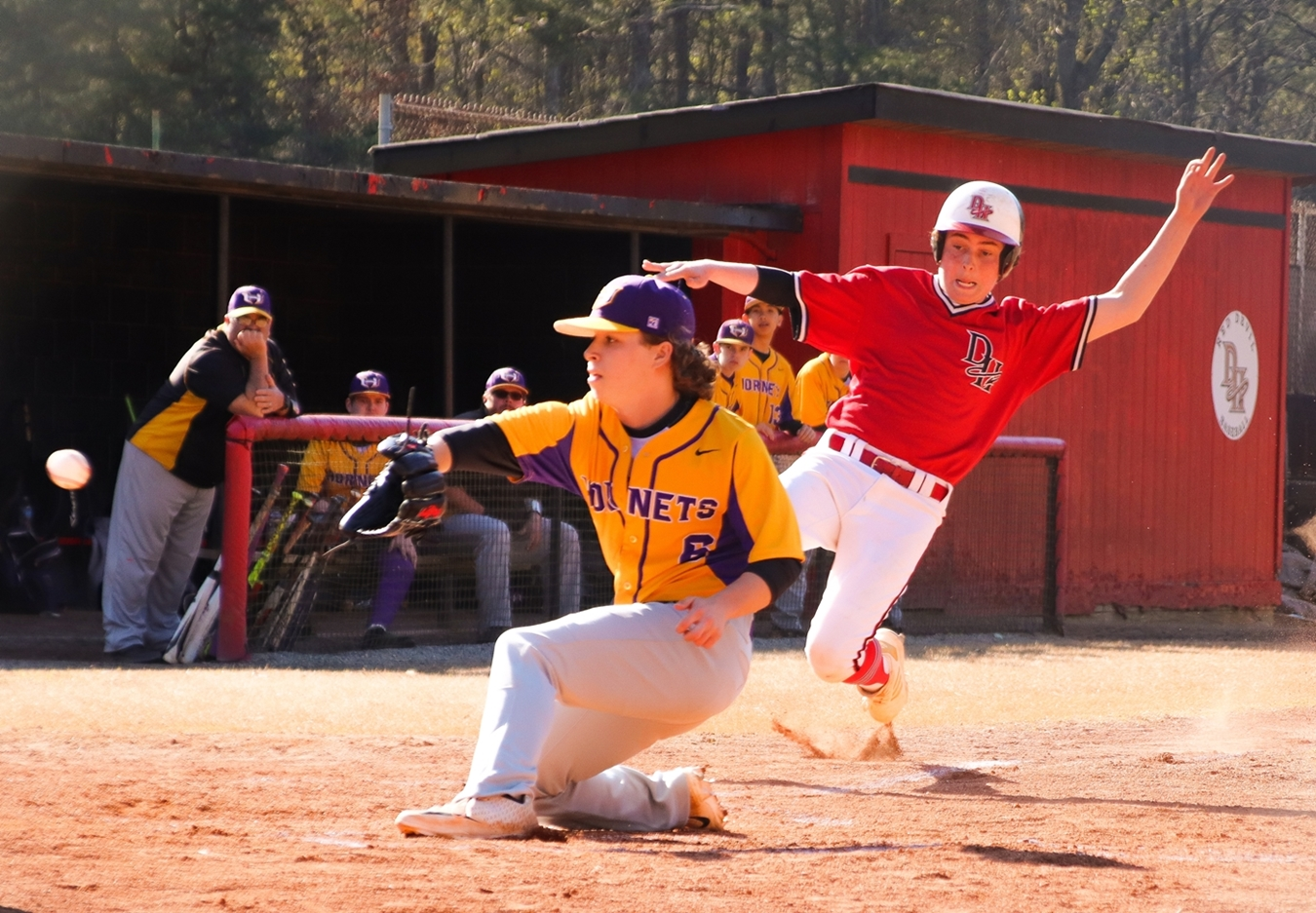 Druid Hills' Daivd McQuaig (right) slides in safe at home ahead of the tag by Hampton pitcher Logan Seehafer. McQuaig took advantage of a wild pitch to score from third on the play. (Photo by Mark Brock)
