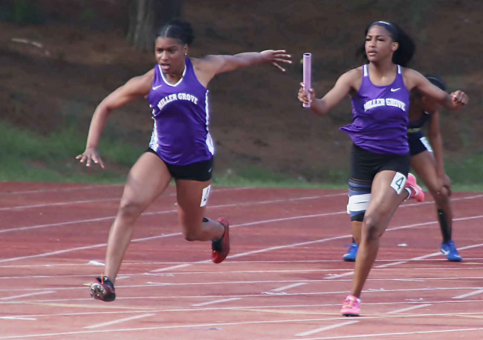 Miller Grove's Tacari Demery (left) took the baton from teammate Chance Barnes and cliched first in the 4x100 meter relay at the DCSD County Championships in March.. The pair hope to lead the Lady Wolverines to a state track championship this weekend. (Photo by Mark Brock)