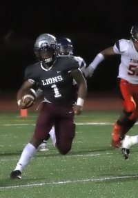 Quarterback Jacobi Haynes accounted for 5 touchdowns and 339 yards of offense in leading the Martin Luther King Jr. Lions to a 41-25 Region 4-6A win over the Mundy's Mill Tigers. (Photo by Mark Brock)