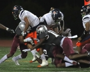 Martin Luther King Jr.'s Colin White (3), Keion Cush (11) and Jomel Robinson (15) combine on a tackle against Mundy's Mill. (Photo by Mark Brock)