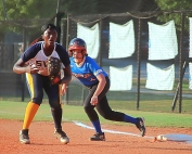 Southwest DeKalb first baseman Aniyah Lee (left) hit a huge fifth inning grand slam homer in the Lady Panthers' 8-6 win over Chamblee's Emily Katz and her teammates at Chamblee on Thursday. (Photo by Mark Brock)