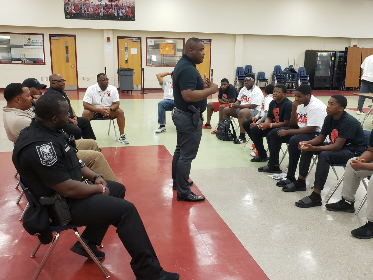 DeKalb County Police officers meet with McNair High football team members as part of the partnership with the NFL and HELP.