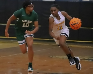 Lithonia's Laila Williams drives against the defensive pressure of Arabia Mountain's Sydney Bunkley (10). Bunkley and her Lady Ram teammates rallied from an early 10-0 deficit for the win at Lithonia. (Photo by Mark Brock)