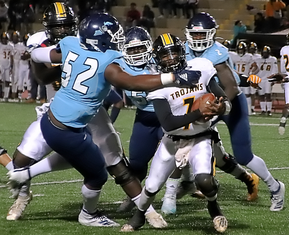 Cedar Grove's Christen Miller gets a grip on Peach County quarterback in 36-3 win last week. (Photo by Mark Brock)