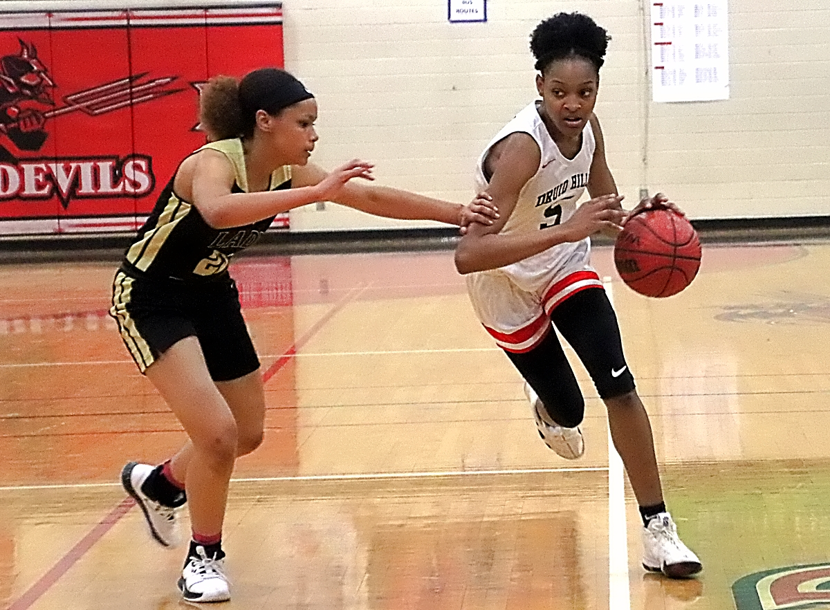 Druid Hills' Natalie Martin (5) streaks up court against McDonough's Heaven Greene (23) during McDonough's Region 4-4A win. (Photo by Mark Brock)