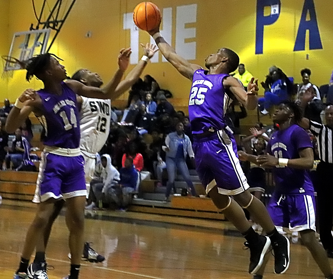 Miller Grove's Jamarcus Glover (25) pulls down one of his 11 rebounds off a missed free throw. He grabbed the ball in front of teammate's Jahmil Barber (14) and Zyair Greene (11) and Southwest DeKalb's Chandler Sanders (12). (Photo by Mark Brock)