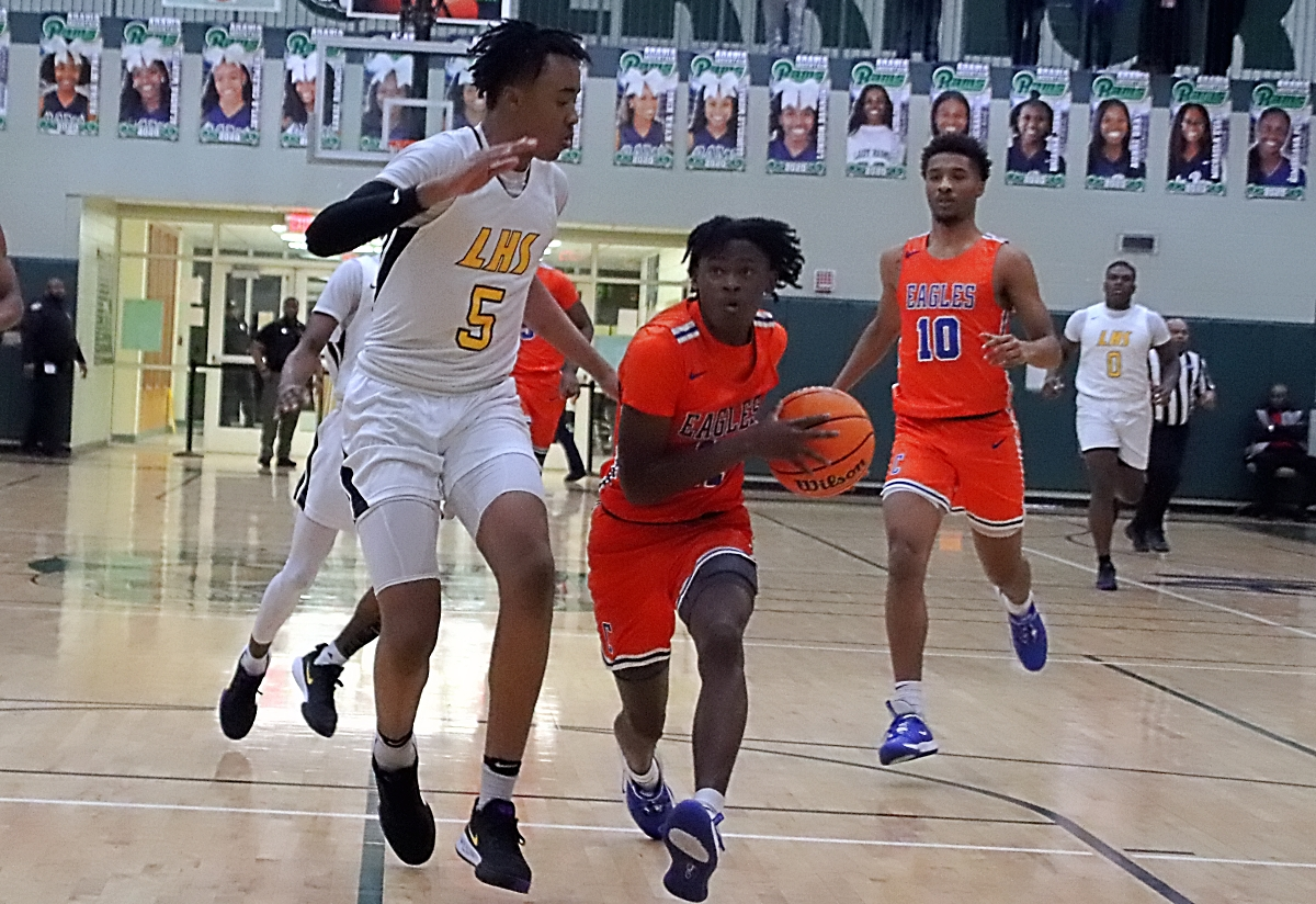 Columbia's Kawasiki Ricks (with ball) drives against Lithonia's Franklin Champion (5) in the Eagle's 82-68 upset of the No. 1 ranked Bulldogs. (Photo by Mark Brock)