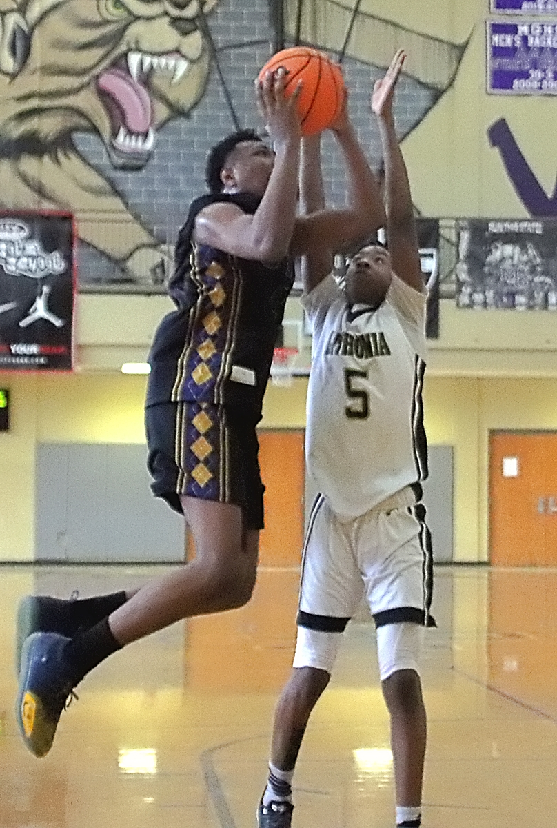 Southwest DeKalb's Kourtney Forrest (with ball) shoots for two of his 19 points against Lithonia's Chase Champion (5). Forrest was named MVP. (Photo by Mark Brock)