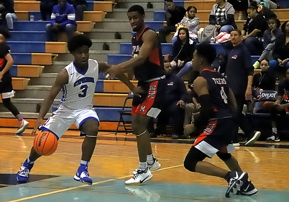 Stephenson's Edwin Walker drives into the lane against a pair Mundy's Mill defenders during Stephenson's win in Region 4-6A play at Lovejoy on Wednesday. (Photo by Mark Brock)