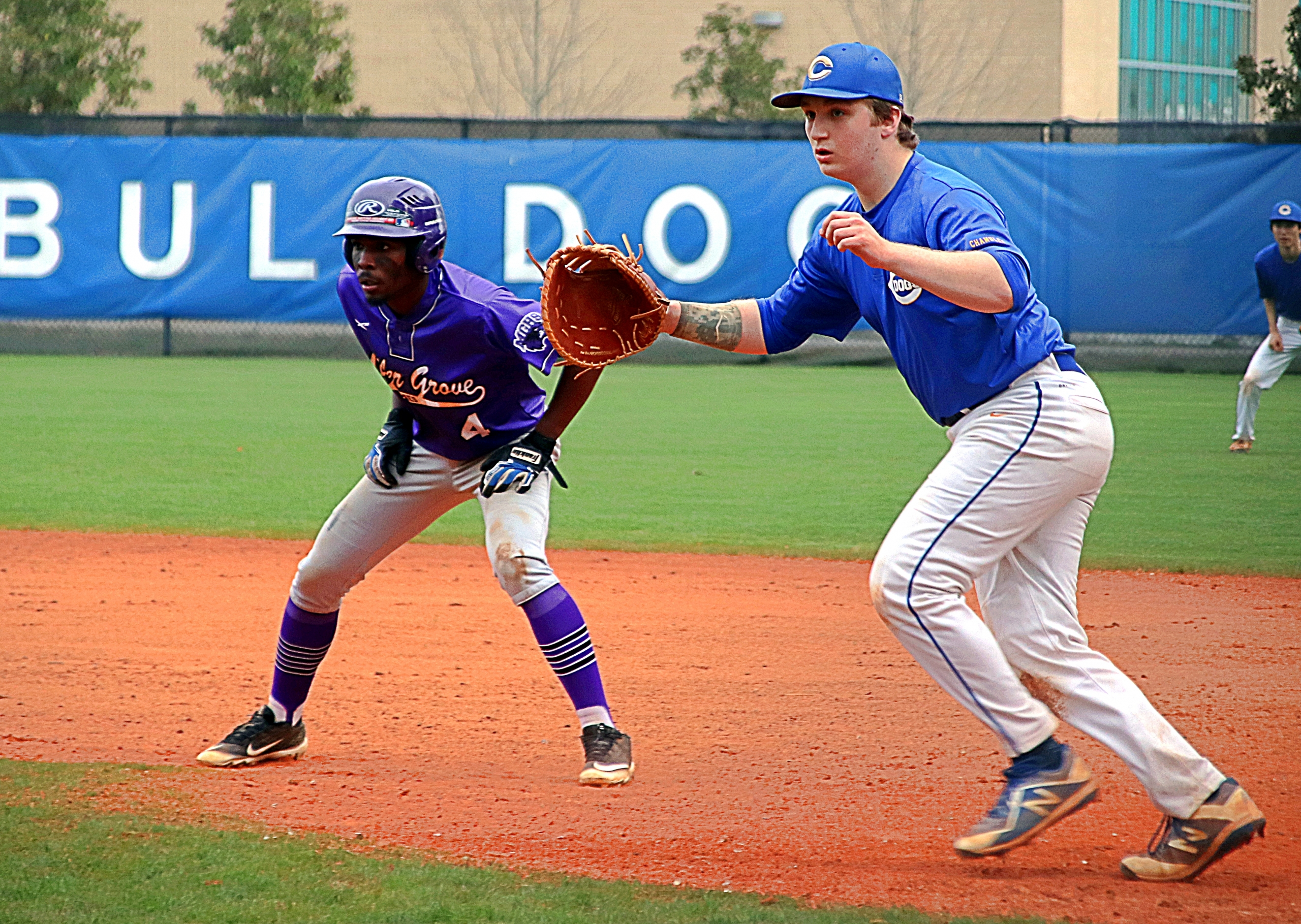 Miller Grove's Jakoby Oliver (4) gets a lead off first as Chamblee first baseman Leon Cohen moves to get in his position on defense. (Photo by Mark Brock)