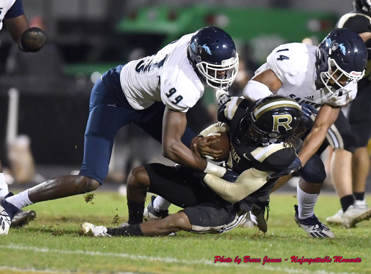 Cedar Grove's Adonijah Green (99) and Dominique Davis III (14) bring down a Rockmart running back. (Photo by Bruce James)
