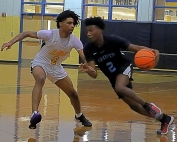 Cedar Grove's Josh Daniels (with ball) drives against Lithonia's Raheem Swain (left) during first half action of Lithonia's 75-43 home victory. (Photo by Mark Brock)