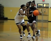 Cedar Grove's Rickayla Johnson (1) avoids Lithonia's Janiya Smith (24) on a drive to the basket. (Photo by Mark Brock)