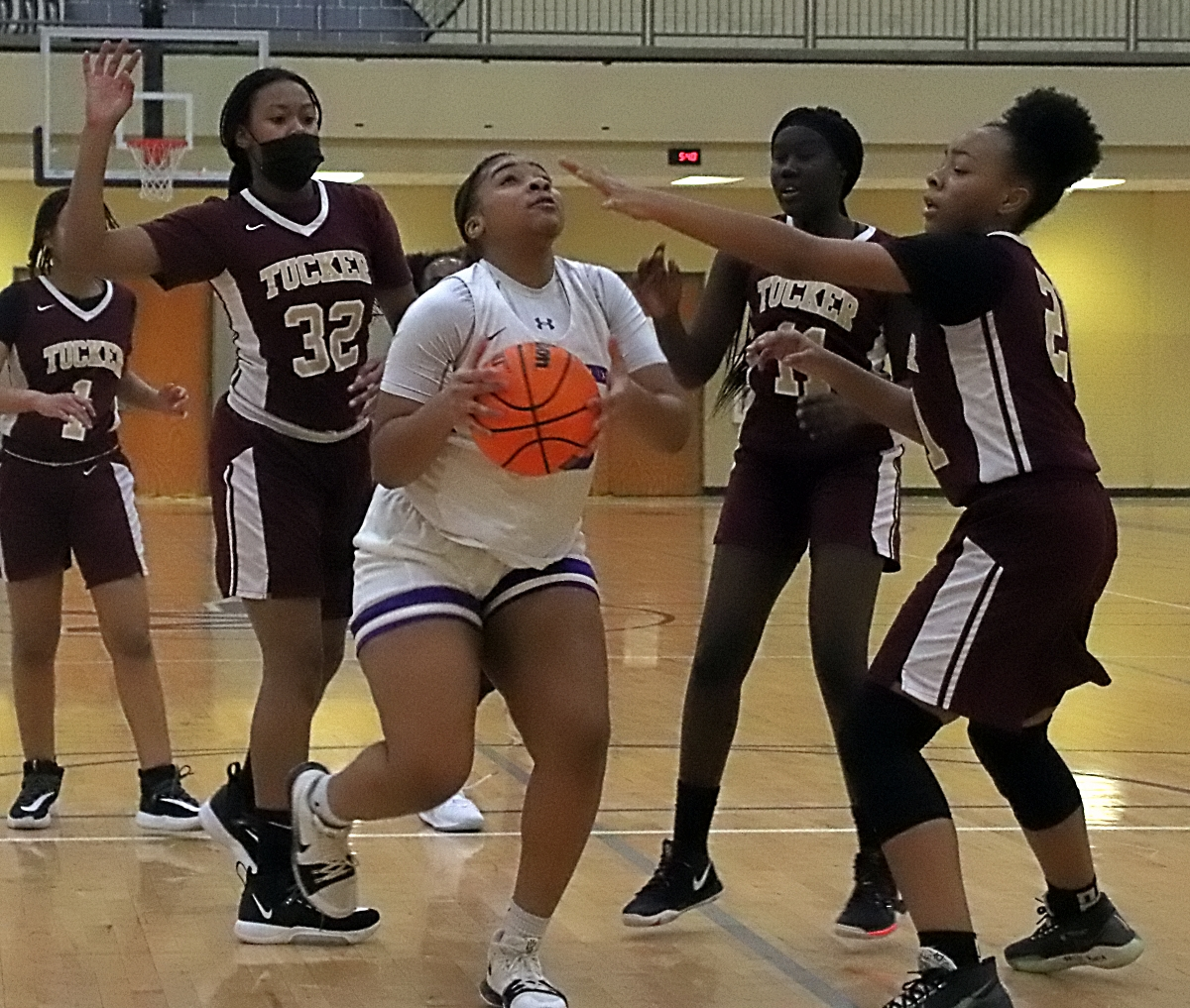 Miller Grove's Jalina Robinson gets in the lane against Tucker defenders Jacinta Hollins (32), Ashoul Yak (11) and Kristan Simmons (21). Robinson keyed a fourth-quarter rally to lead Miller Grove to a 43-35 win. (Photo by Mark Brock)