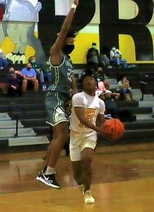 Lithonia's Demetrice Jones  (12) gets Greenbrier's Khaleel Pratt (22) off his feet on a drive to the basket during the second half of the Bulldogs' 62-53 Class 5A boys' first round victory. (Photo by Mark Brock)