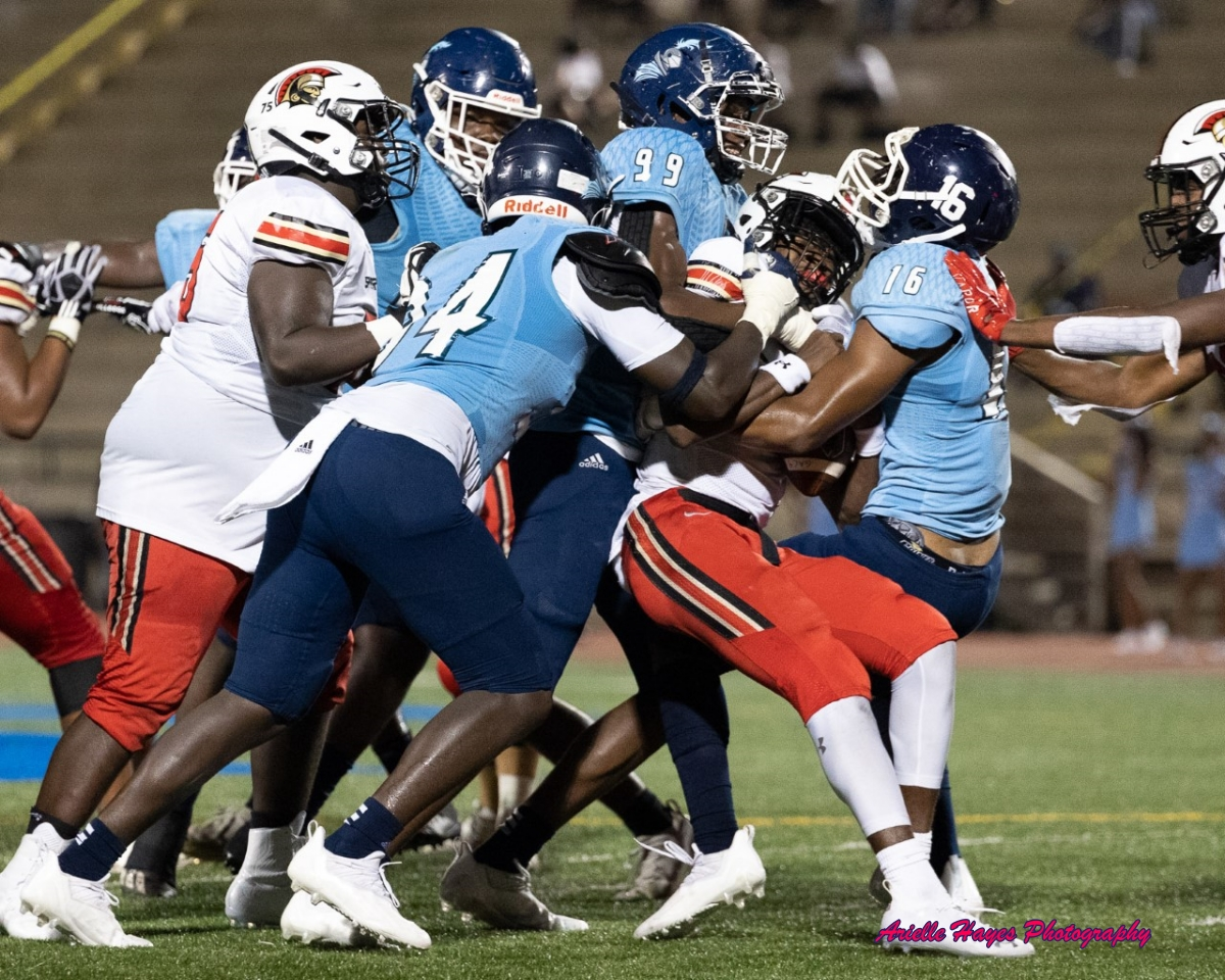 Cedar Grove's Adonijah Green (99) and Cameron Jackson (16) team up with a couple of teammates on a tackle during the Saints' 47-0 shutout of Greater Atlanta Christian last Friday night. (Photo by Arielle Hayes Photography)