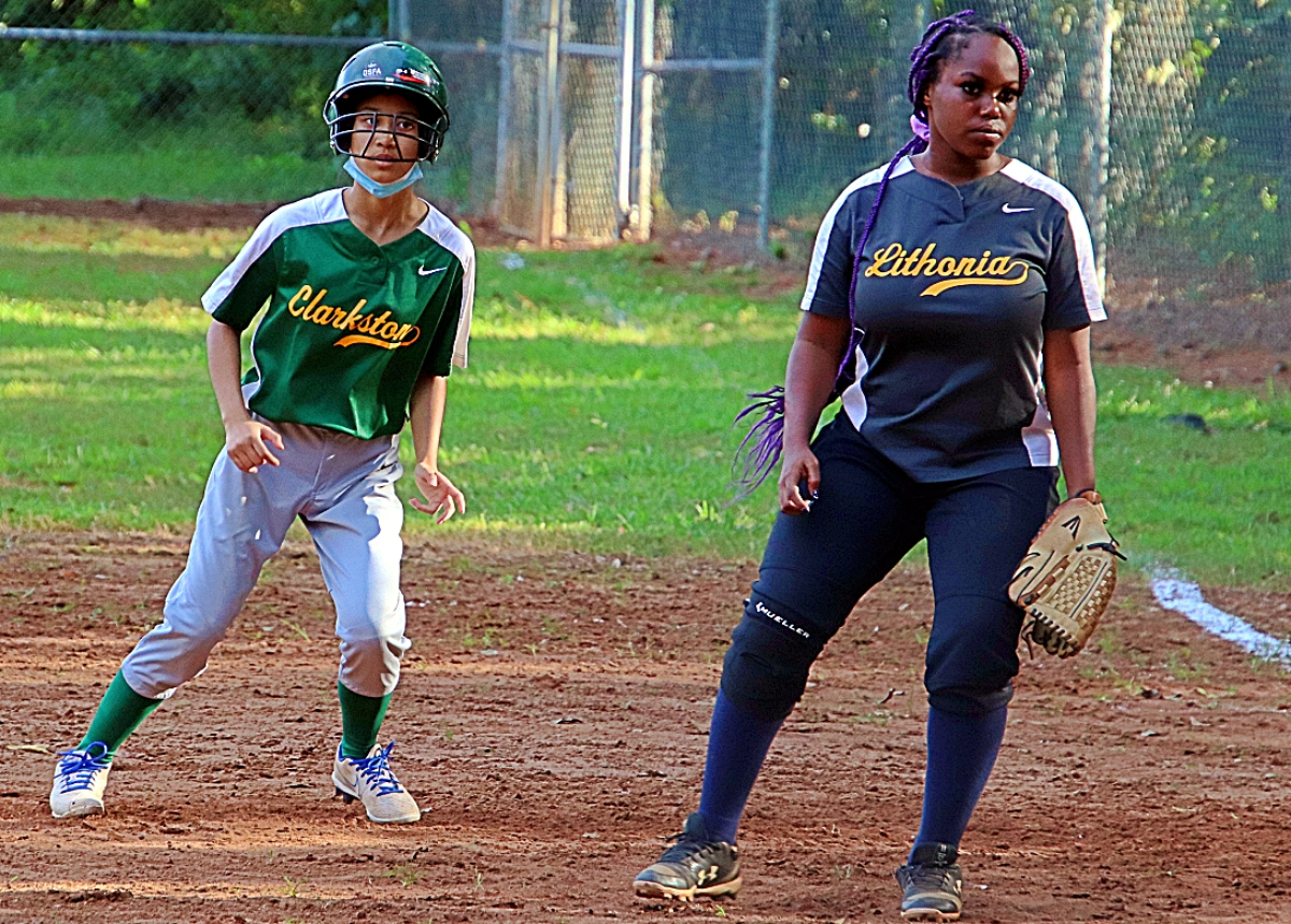Clarkston's Rah K La (left) checks Lithonia first baseman Kaliyah Poole (right) after getting a lead on a pitch during Lithonia's 22-10 win in Region 5-5A girls' softball action. (Photo by Mark Brock)
