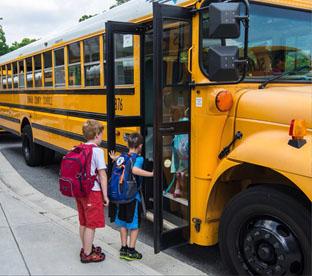 two children boarding a school bus