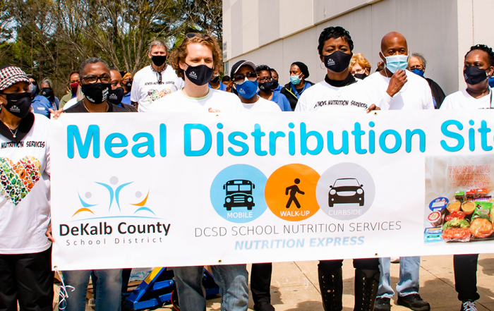 people walking with meal distribution banner