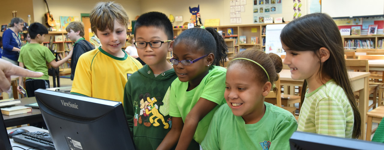 Students looking at a computer screen | social-media-guidelines
