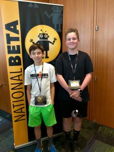 Eli and Ryan smile in front of beta club sign