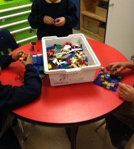 box of legos on red table with hands of 3 students