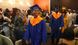 male graduate smiles as he leaves graudation