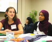 two female students talk at table