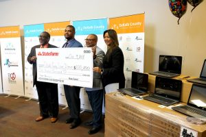 DCSD and State Farm leaders hold large check next to laptops