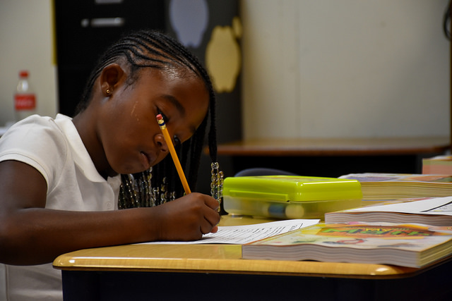 female student focused while writing on paper