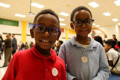 two boys smile with new glasses