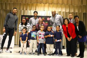 Hawks players, district officials and students smile on stage